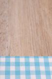 Light blue checkered cloth with blurred wood. As background Royalty Free Stock Photo