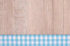 Light blue checkered cloth on wood. As background Royalty Free Stock Photos
