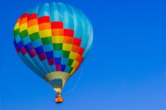 Light Blue Checkered Hot Air Balloon. Against Blue Background Stock Photo