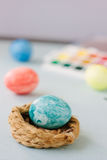 Light blue color easter egg on nest over bright background. Royalty Free Stock Images