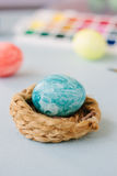 Light blue color easter egg on nest over bright background. Royalty Free Stock Photography