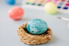 Light blue color easter egg on nest over bright background. Royalty Free Stock Photos