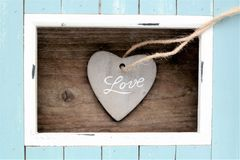 Light blue colored frame and stone heart with the word Love. Light blue and white colored wood frame and stone heart with the word love with natural wooden royalty free stock image