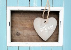 Light blue colored frame and stone heart with the word Love. Light blue and white colored wood frame and stone heart with the word love with natural wooden royalty free stock photography