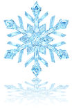 Light blue crystal snowflake on glossy white Royalty Free Stock Images