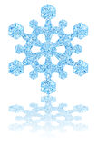 Light blue crystal snowflake on glossy white background Stock Photography