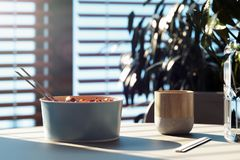 Light dish plate with chopsticks and stylish mug on wooden table. 3d rendering. stock photo