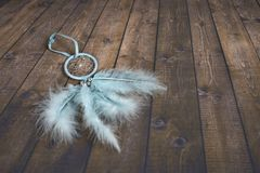 Light blue dreamcatcher on dark wooden background royalty free stock photo