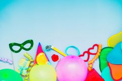 Light blue Festive background with party tools and decoration - baloons, funny carnival masks, festive tinsel. Happy birthday gree. Ting card. Design concept royalty free stock photo