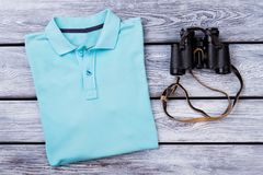 Light blue folded polo t shirt and binoculars. Top view. Wooden desk surface background Stock Photos