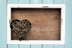 Light blue frame and rusted nails, in a heart shape. Light blue and white colored wooden frame, lots of nails put together in a heart shape, in the middle a Stock Image