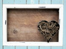 Light blue frame and rusted nails, in a heart shape. Light blue and white colored wooden frame, stone heart with the word love, natural wooden background, Father royalty free stock image