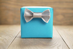 Light blue gift box with minimalistic silver ribbon bow on wooden Stock Images