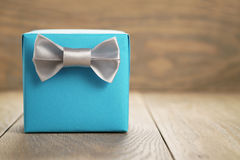 Light blue gift box with minimalistic silver ribbon bow on wooden Stock Image