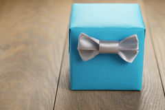 Light blue gift box with minimalistic silver ribbon bow on wooden table Stock Photography