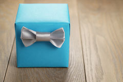 Light blue gift box with minimalistic silver ribbon bow on wooden table Royalty Free Stock Photo