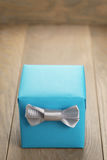 Light blue gift box with minimalistic silver ribbon bow on wooden table Royalty Free Stock Photography