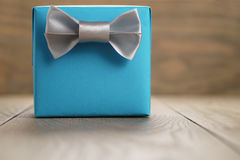 Light blue gift box with minimalistic silver ribbon bow on wooden table Royalty Free Stock Image
