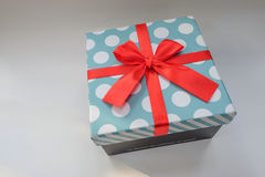 Light blue gift box with white polka dot. And red ribbon Royalty Free Stock Photo