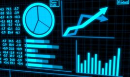 Financial Charts and Statistics screen glowing light blue. Stock Photos