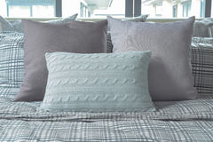 Light blue and gray pillows on cross pattern bedding. At home Stock Photo