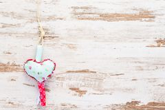 Light blue heart on vintage background. Light blue handmade heart on a string at a vintage wooden background. Can be used for postcard, wishing posts and Royalty Free Stock Image