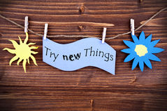 Light Blue Lable Saying Try New Things. On Wooden Background Hanging On A Line, One Blue Flower Symbol And One Yellow Sun Symbol Background Is Old Fashion Royalty Free Stock Images