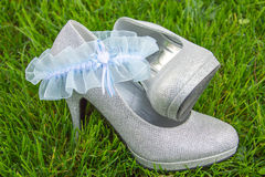 Light blue lace garter arranged with silver high heel shoes Royalty Free Stock Photography