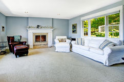 Light blue living room with white sofa and fireplace. Light blue living room with white sofa, armchair and leather chair and cozy fireplace Royalty Free Stock Photography