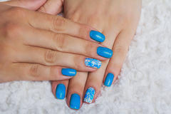 Light blue nail art with flowers on textile Royalty Free Stock Image