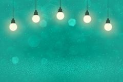 Light blue wonderful sparkling glitter lights defocused bokeh abstract background with light bulbs and falling snow flakes fly, royalty free illustration