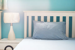 Light blue pillow on white  bed Royalty Free Stock Images