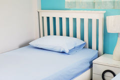 Light blue pillow on white  bed Royalty Free Stock Image