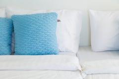 Light blue pillows white bed Stock Image