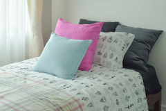 Light blue and pink pillow on single bed size Stock Photos