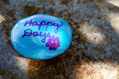Light blue rock with the words & x22;Happy Days& x27; painted in purple. A stone is painted light blue and has the message & x22;Happy Days& x22; painted in stock image