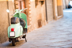 Light blue scooter on the street of the old city. Old classic european city elements. Light blue retro scooter on the street of the old city Royalty Free Stock Images