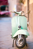 Light blue scooter on the street of the old city. Old classic european city elements. Light blue retro scooter on the street of the old city Stock Photo