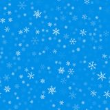 Light blue snowflakes pattern on blue Christmas. Light blue snowflakes pattern on blue Christmas background. Chaotic scattered light blue snowflakes. Fantastic Royalty Free Stock Photos