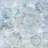 Light blue vintage doily grungy background. Blue and green floral vintage grungy background with antique text Stock Photos