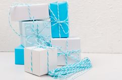 Blue and white gift boxes with ribbon. Light blue and white gift boxes with ribbon on white table. Holiday concept, copy space stock photography