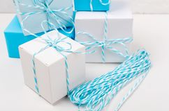 Blue and white gift boxes with ribbon. Light blue and white gift boxes with ribbon on white table. Holiday concept, copy space royalty free stock photo
