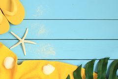 Summer vacation background with yellow towel, flip flops. palm leaf and seashells royalty free stock photos
