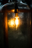 Light in a Bottle. This light fixture was in a small cabin I was visiting. The light was in a large bottle sitting on a window sill. The dark behind the light Royalty Free Stock Images