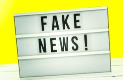 Light box with the headline Fake News with against yellow background. Blog concept image stock photos