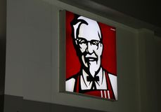 The light box of Kentucky fried chicken logo on the wall at night in front of Tesco Lotus. stock photo