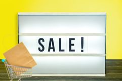 Light box with Sale letters and small shopping cart against yellow background on table stock photography
