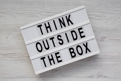 Light box with `Think outside the box` words on a white wooden surface, top view. Flat lay, overhead, from above. Close-up.  royalty free stock image