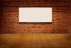Light box or white board on brick grunge wall and wood floor in room Royalty Free Stock Photography