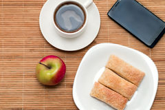 Light breakfast. A light breakfast - a cup of coffee with pastries and a phone on the table Royalty Free Stock Photos